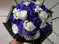 Hand Tied Bouquet with Ivory Roses, Blue Hydrangeas, White Bouvardia edged in Aspidistra Leaves and Bear Grass