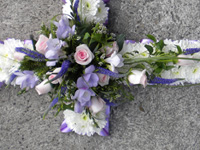 Cross Funeral Tribute - Edged in Ribbon, based in White Chrysanthemums with a spray of flowers in Pink, Lilac and Purple